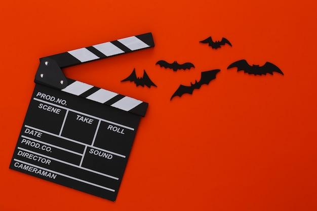 Filme de terror, tema de halloween. claquete de cinema e morcegos decorativos voadores em laranja