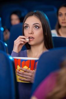 Filme incrível! jovem animada comendo pipoca e assistindo filme enquanto está no cinema
