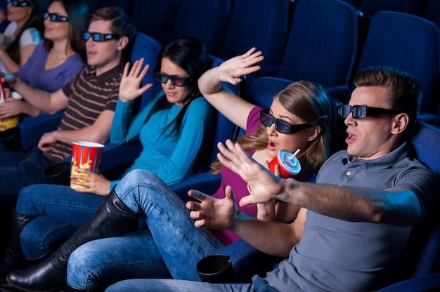 Filme muito realista. vista superior de pessoas em óculos tridimensionais assistindo filme e gesticulando enquanto estão sentadas no cinema