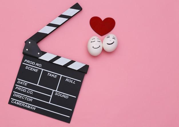 Filme romântico. claquete e ovos de rosto enamorado com um coração em um fundo rosa. vista do topo