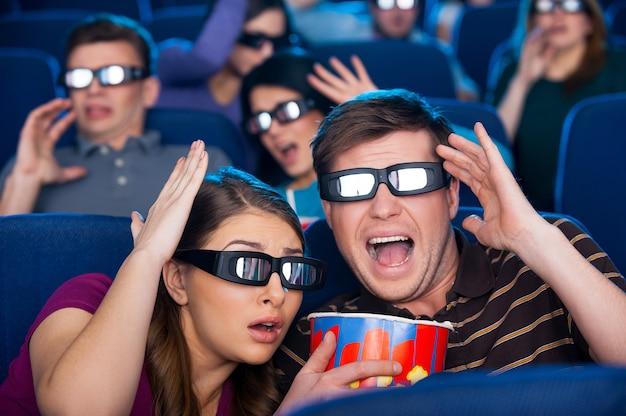 Filme tão realista! jovens chocados em óculos tridimensionais gesticulando enquanto assistiam a um filme no cinema juntos