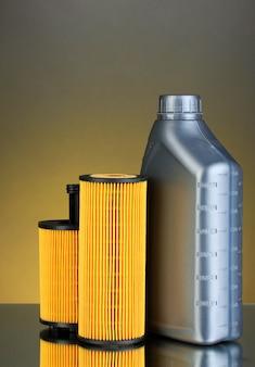Filtros de óleo de carro e óleo de motor podem na superfície de cor escura