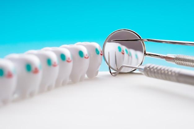 Fim acima. ferramentas dos dentes e modelo dos dentes do sorriso no fundo branco.