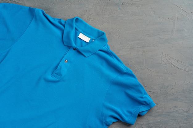 Fim azul da textura do t-shirt do polo do algodão acima. moda masculina