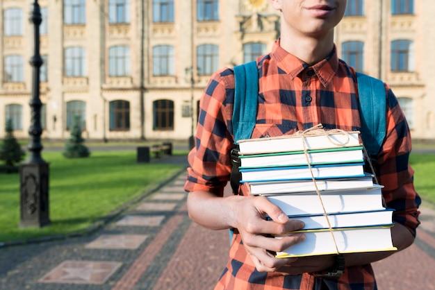 Fim, cima, adolescente, menino, segurando, livros