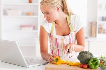 Fim, cima, mulher, usando, laptop, cozinhar