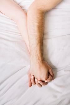 Fim, cima, par, segurando, mãos, cama