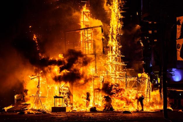 Fim das festividades valencianas de fallas, monumento caído consumido no fogo em altas chamas.