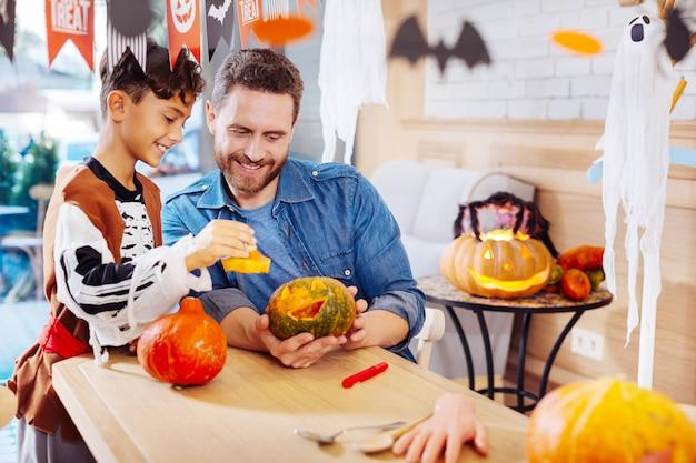 Fim de semana com filho. pai barbudo adorável passando o fim de semana com o filho se preparando para a celebração do halloween