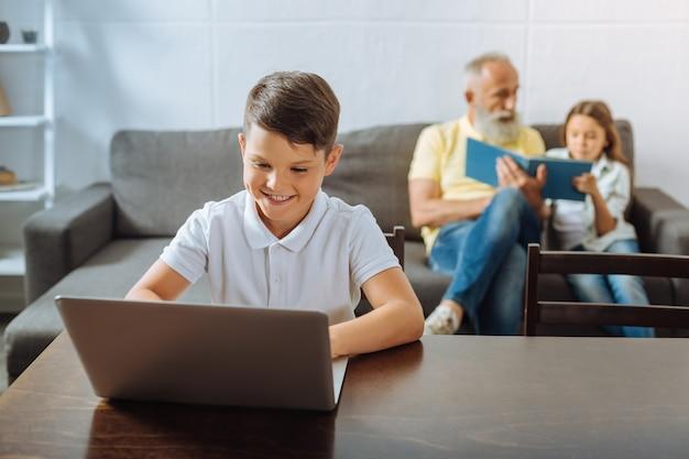 Fim de semana descontraído. garoto simpático e fofo jogando no laptop enquanto o avô e a irmãzinha lêem um livro azul juntos no sofá