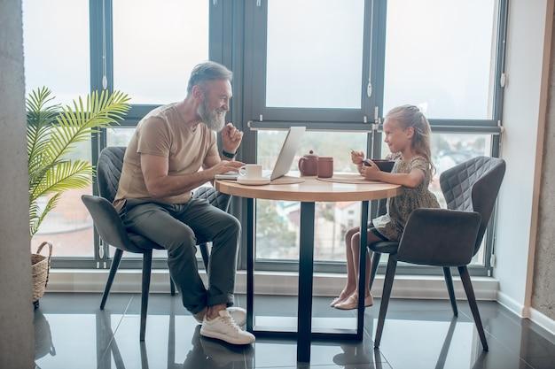 Fim de semana em família. um homem e sua filha sentados à mesa, homem trabalhando, sua filha comendo