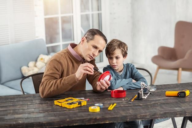 Fim de semana juntos. homem bonito e sério de cabelos escuros mostrando instrumentos para o filho enquanto está sentado na mesa e o ensinando
