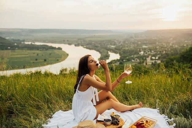 Fim de semana no piquenique. garota na grama verde no piquenique, comendo cereja e beber vinho.