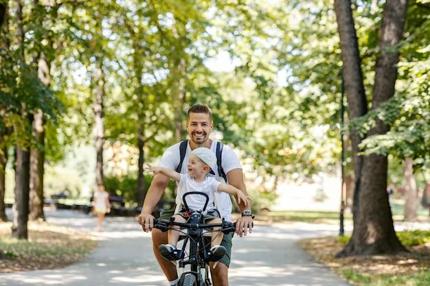 Fim de semana para atividades familiares. o menino está sentado em uma cesta de bicicleta enquanto seu pai anda de bicicleta pela floresta. pai e filho se relacionando, estilo de vida saudável, brincando