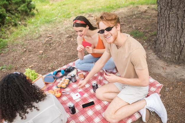 Fim de semana, piquenique. vista superior de jovens amigos otimistas jogando cartas em xadrez xadrez fazendo piquenique no verão