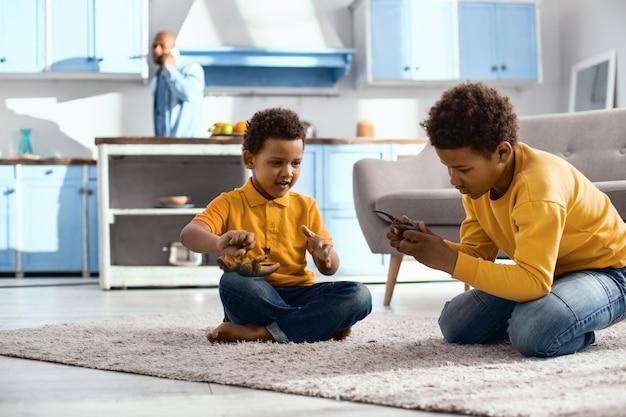 Fim de semana tranquilo. meninos encantadores sentados no tapete brincando com dinossauros de brinquedo enquanto o pai os observa ao fundo