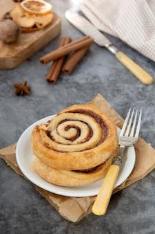 Fim do bolo do rolo de canela acima. redemoinho de canela pastelaria no café da manhã em cinza