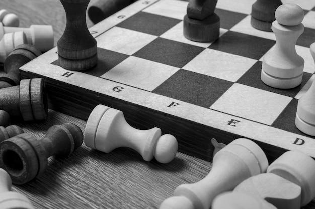 Fim do jogo de xadrez, as peças de xadrez ficam perto do tabuleiro de xadrez na mesa, vista de cima, preto e branco.