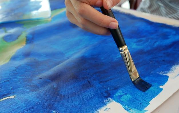 Fim macio do foco acima da mão da criança que pinta a cor azul na lona.
