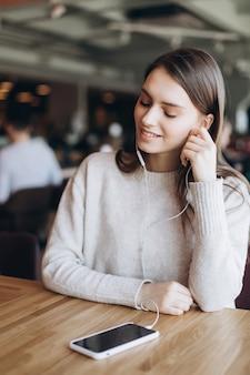 Fim natural da cara da mulher bonita acima da menina ocasional da beleza do estilo de vida do retrato fêmea com smartpone no café