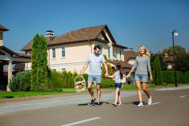 Final-de-semana encantador. pais jovens e agradáveis e sua linda filha caminhando juntos pela rua e indo para um piquenique de mãos dadas