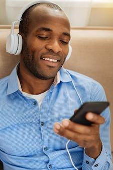 Final de semana. jovem bonito e exuberante de cabelos escuros usando fones de ouvido, segurando um telefone e ouvindo música enquanto relaxa no sofá com os olhos fechados