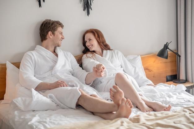 Final de semana. um casal deitado na cama e parecendo em paz