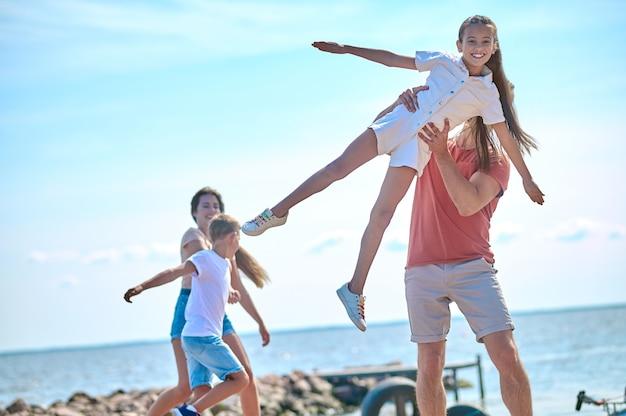 Final de semana. uma família passando um tempo na praia e se sentindo incrível