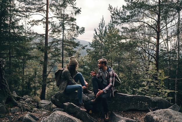Finalmente aproveitando a viagem. lindo casal jovem sentado nas rochas e conversando enquanto caminham juntos na floresta