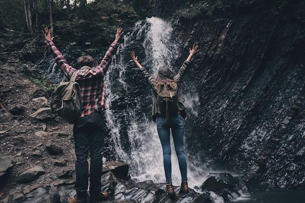Finalmente aqui! retrovisor de corpo inteiro de um jovem casal levantando as mãos em pé perto da cachoeira