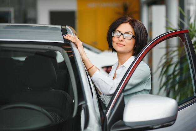 Finalmente carro novo! jovem cliente do sexo feminino verificando um carro novo na concessionária, escolhendo decisão de compra, compra, consumismo, conceito de transporte de veículo de segurança