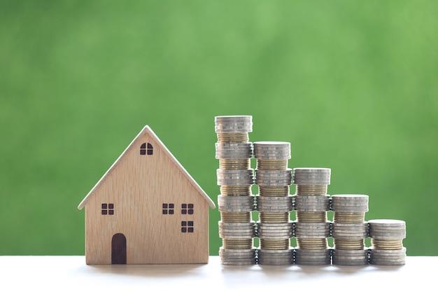 Finanças, casa modelo com pilha de moedas em fundo verde natural, economia para preparar no futuro e conceito de investimento