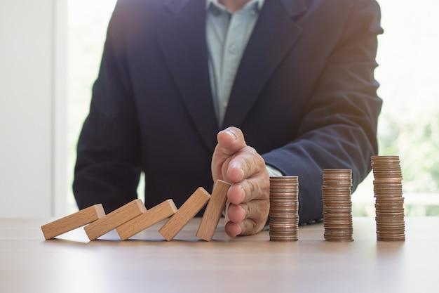 Finanças de proteção do conceito de efeito dominó. as mãos param o efeito dominó antes de destruir a pilha de dinheiro.