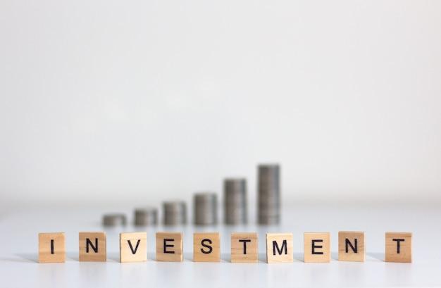 Finanças e investimento conceito. moedas e cubo de madeira de palavra investimento fundo da pilha