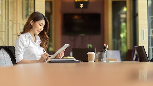Financeira atraente lendo nota fiscal em mulher de negócios tablet digital usando tablet