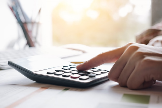 Financie o conceito, a mulher que usa a calculadora com analisa a carta do gráfico e o laptop do computador para a previsão de lucro no futuro.