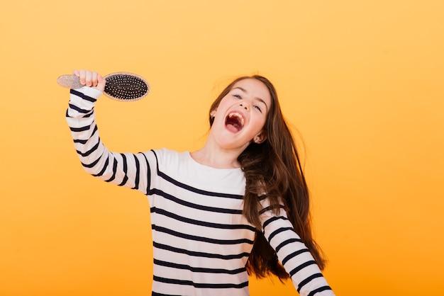 Fingindo superstar, pequena garota ouvindo música. educação musical, canto do microfone com escova de cabelo e desenvolvimento da voz.