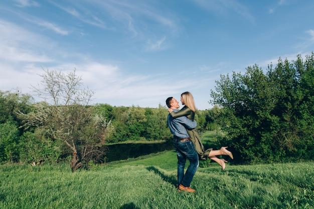 Fins de semana jovem família fora da cidade em dia ensolarado. feliz casal apaixonado andando no parque primavera.