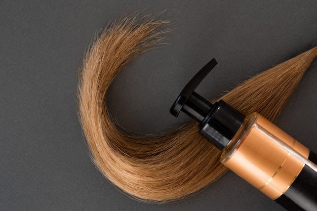 Fio de cabelo loiro e um produto de cuidado. fundo preto. conceito de beleza