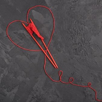 Fio de lã vermelho e agulhas na ardósia