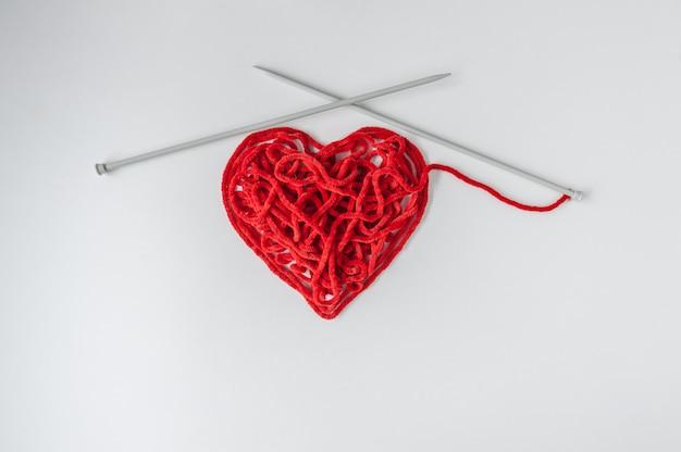Fio de tricô vermelho com agulhas, em forma de coração. dia dos namorados conceito mínimo.