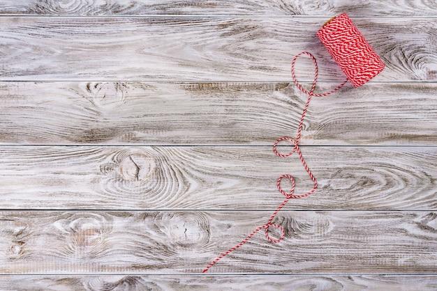 Fio decorativo vermelho e branco de natal na mesa de madeira clara.