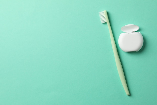 Fio dental e escova de dentes no fundo da casa da moeda, espaço para texto