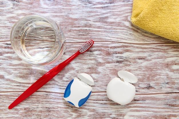 Fio dental, escova de dentes, copo de água e toalha, artigos de higiene pessoal