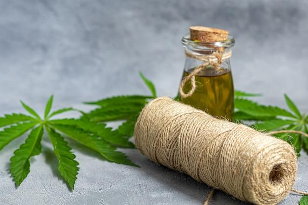 Fio feito de cannabis e folhas de cânhamo em um fundo cinza.