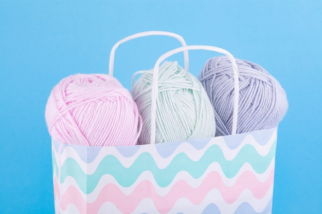 Fio para tricotar delicadas cores pastel em um saco de papel multicolorido sobre um fundo azul.