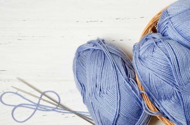 Fios azuis e agulhas de tricô em uma cesta de vime redonda