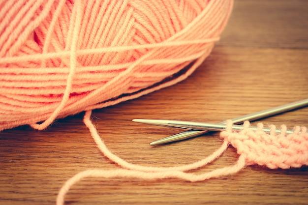 Fios bege e agulhas de tricô. imagem enfraquecida.