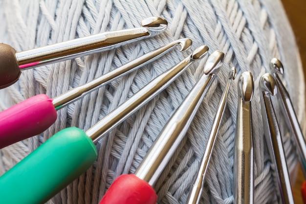 Fios cinzentos para crochet e um conjunto de ganchos multicoloridos.