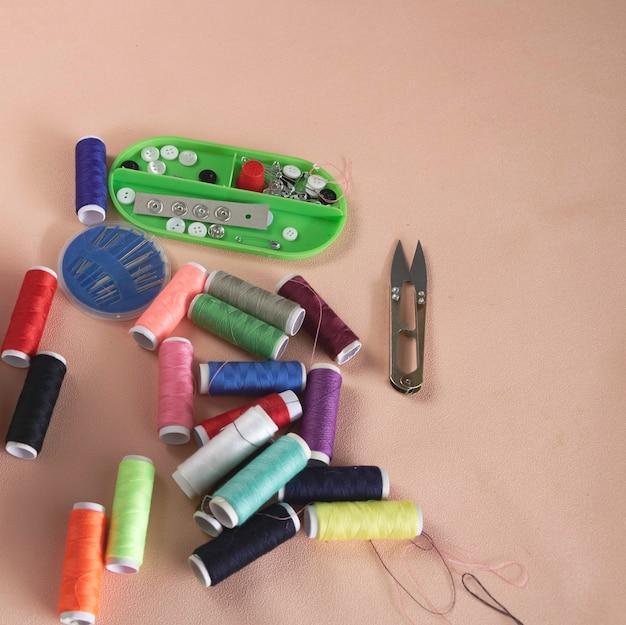 Fios coloridos, caixa de agulha e bandeja de botões colocam pastel no fundo. ferramentas para trabalho com agulha